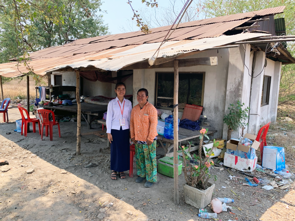 Sothea and her mom stand in front of a dilapidated house smiling with holes in the roof and debris everywhere